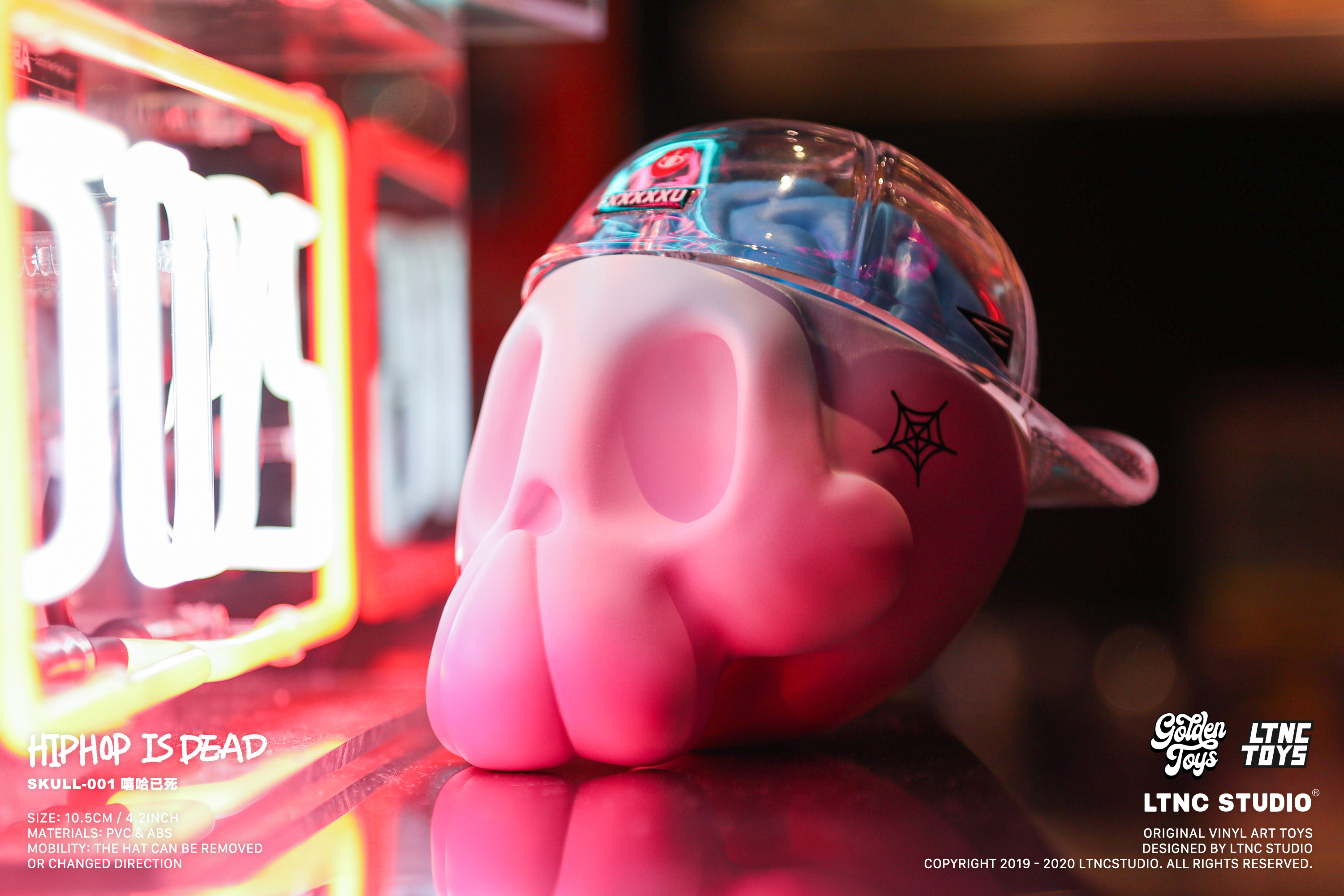 Blue and pink skull toy placed on surface pointing sideways towards neon lights