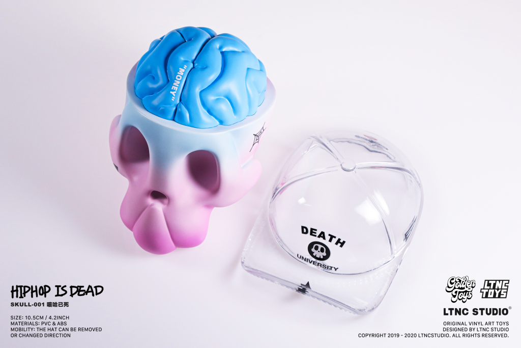A pink and blue skull toy with baseball cap removed to show blue brain