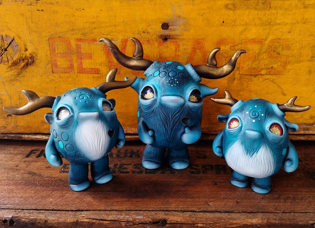 three owlberry lane monster sculpts standing on a wooden surface