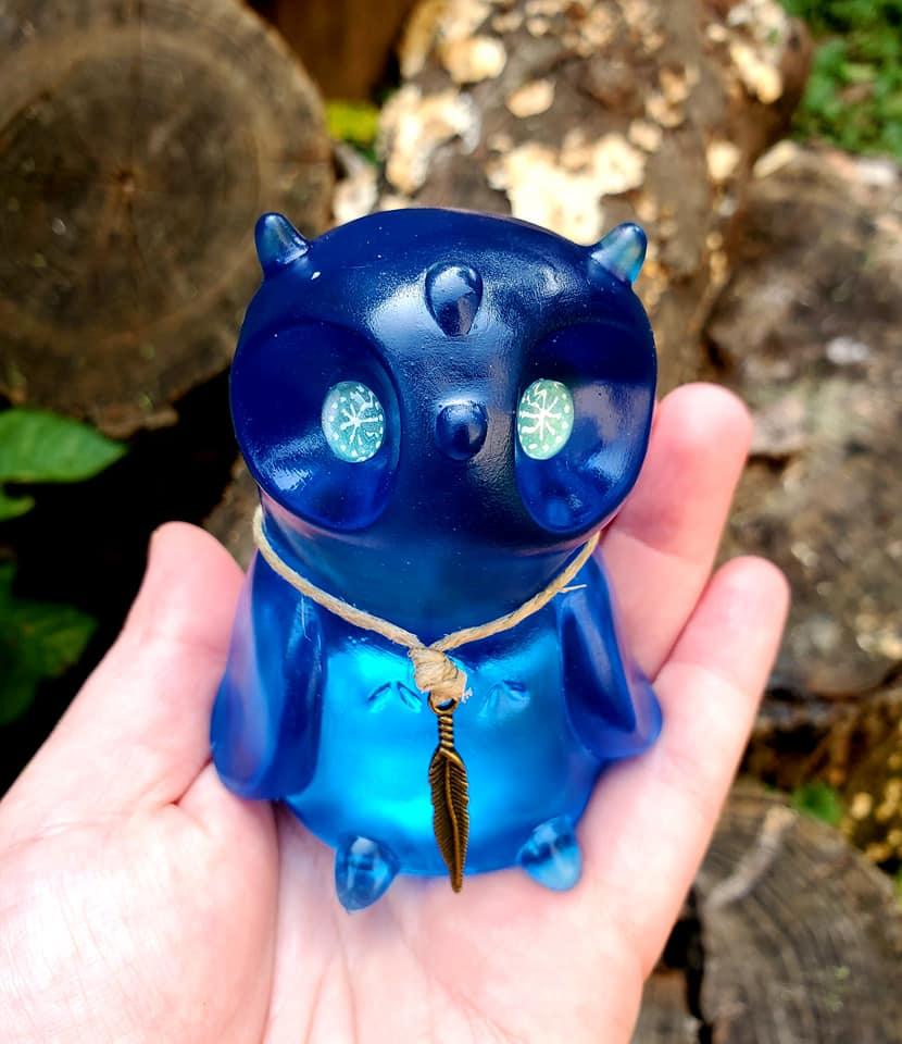 A blue toned owl with a necklace whilst against a woodland background