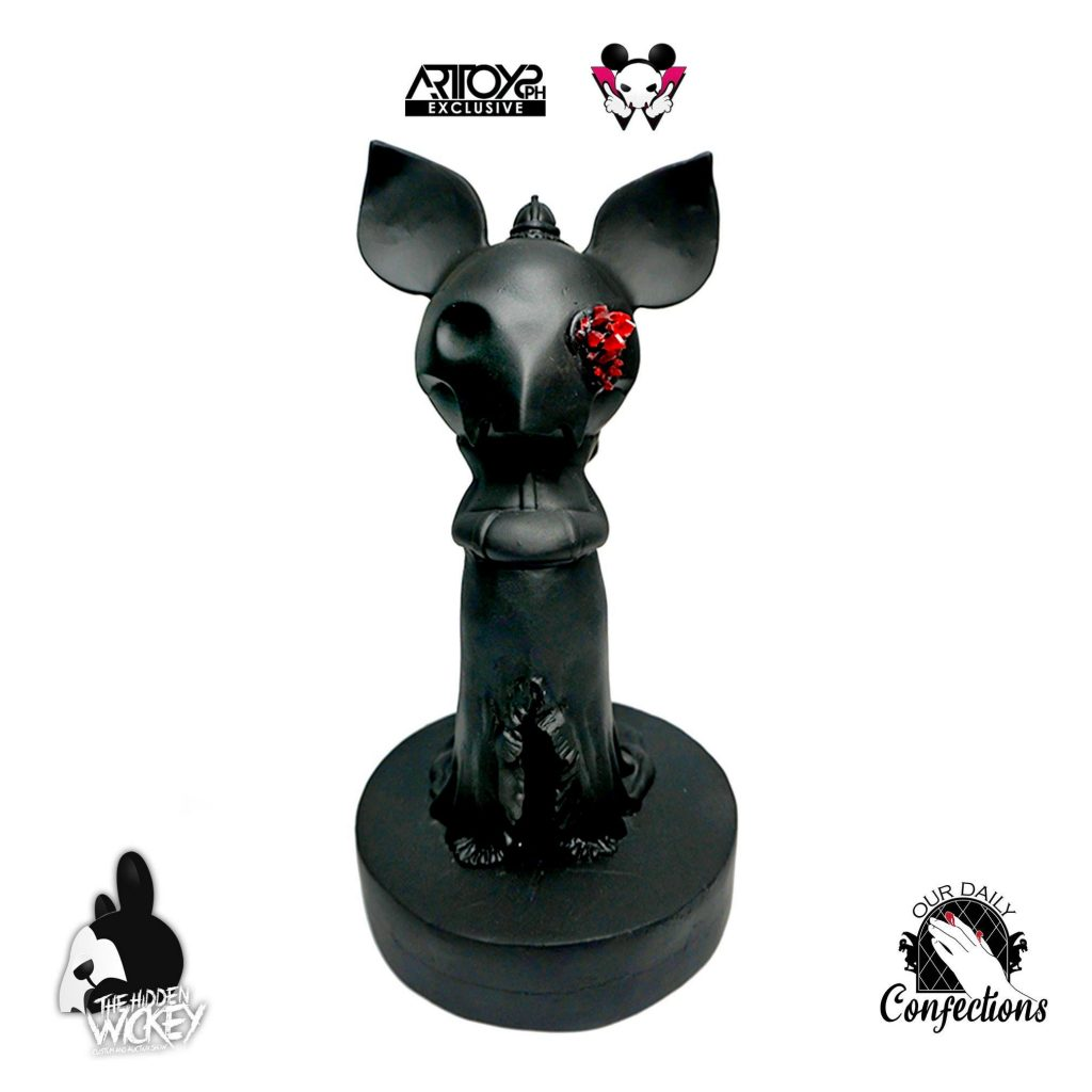 A black gothic looking rat toy with red crystals in the left eye