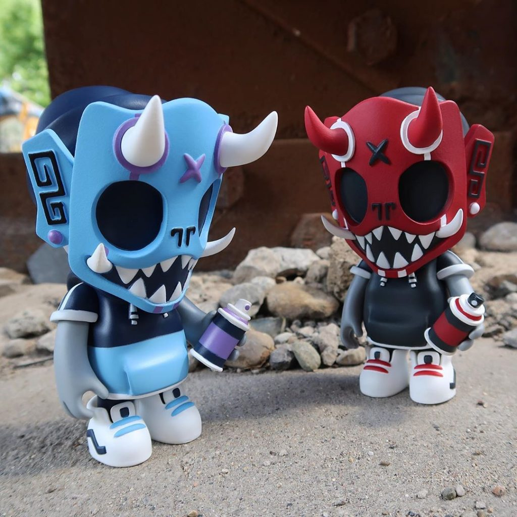 chris dokebi puck little painter og red and blue versions standing in front of rubble