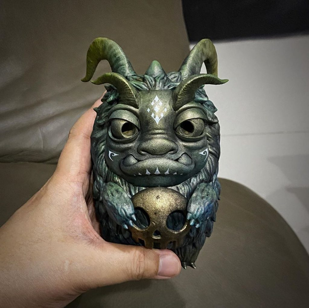 A metallic looking furry monster toy with horns