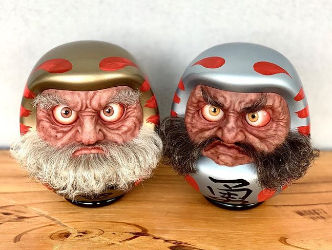 Look into the eyes of the gold and silver Daruma.